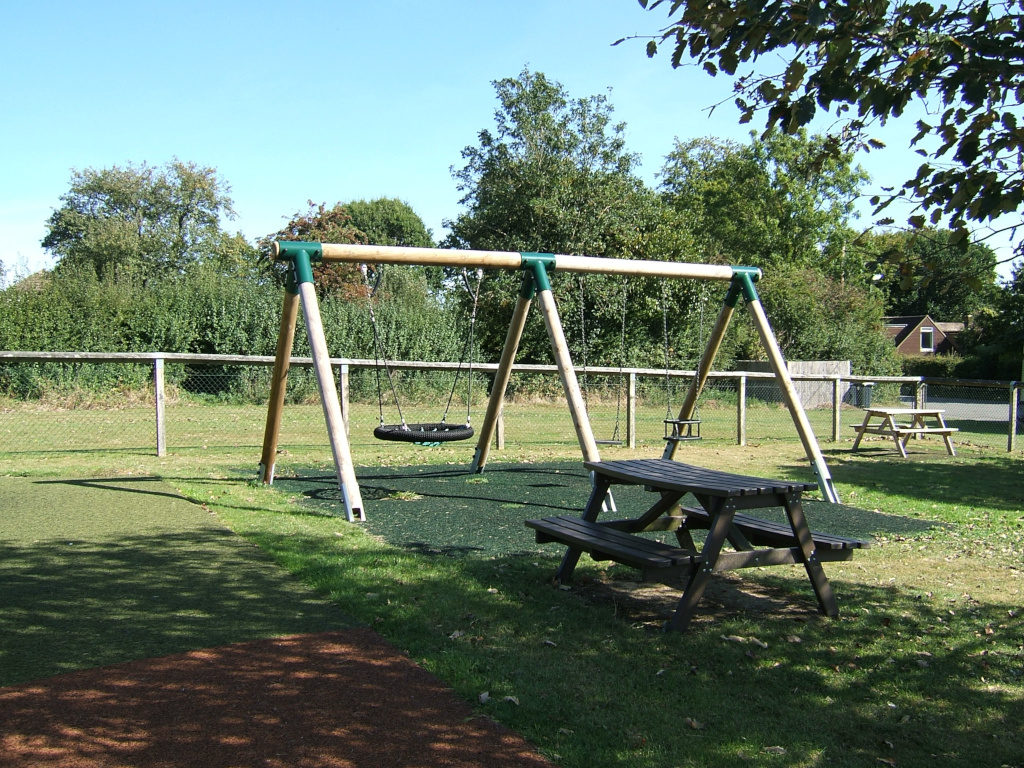 Swings and picnic tables in the children's play area